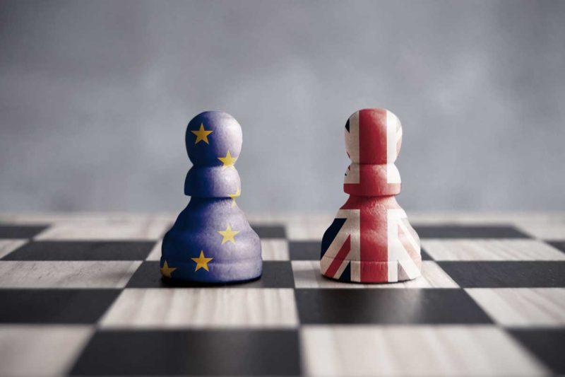Zwei Schachfiguren mit Europa und UK Flagge