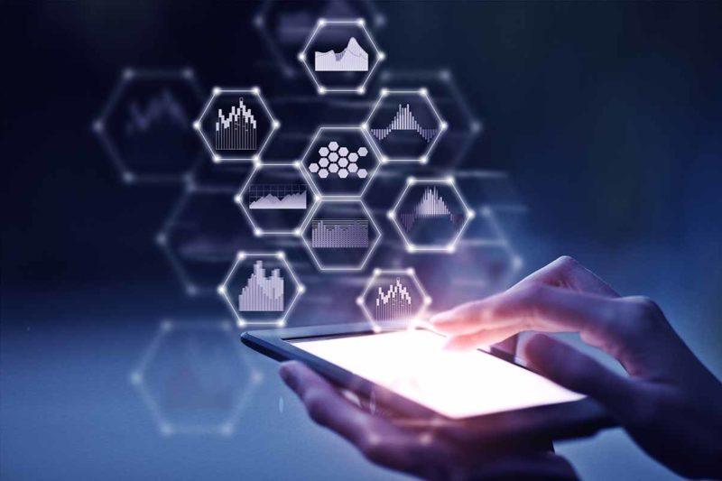 Man sieht Hände, die ein Tablet halten und Datensymbole.