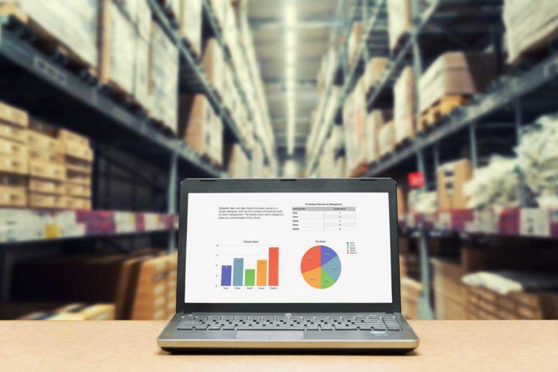 Ein Laptop der in einem Warenlager steht und zum Stammdatenmanagement genutzt wird.