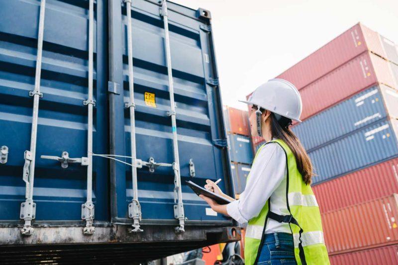 Eine Frau, die einen Container für das Zollverfahren prüft.