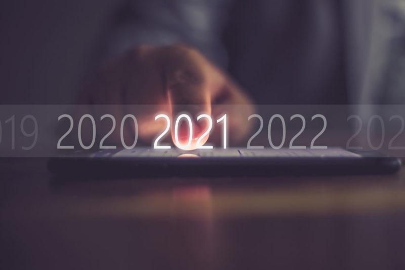 Im Hintergrund eine Hand, die auf ein Tablet zeigt und im Vordergrund leuchtet die Zahl 2021 auf einem Zeitstrahl.
